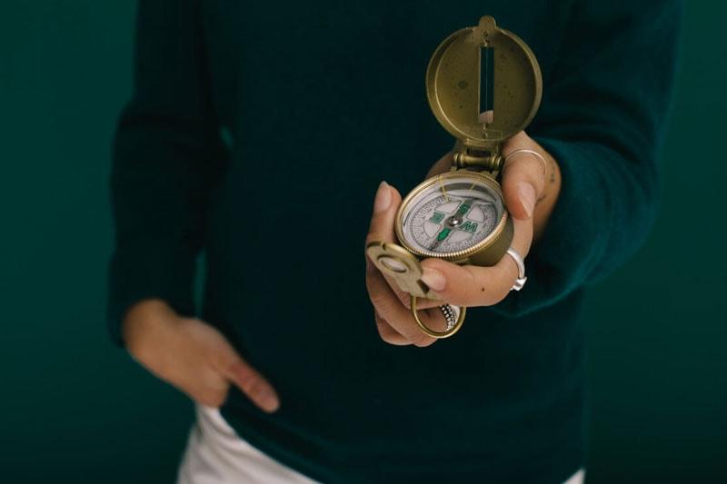 Eine Frau trägt einen Kompass in der Hand